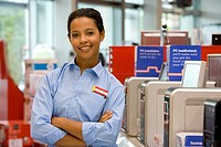 Computer saleswoman in shop with arms crossed, smiling, portrait (thumbnail)