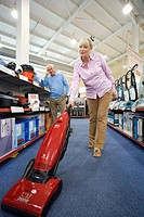 Mature couple shopping for hoover, low angle view