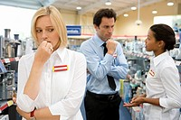 Young saleswoman with hand to face, colleagues in conversation in background