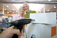 Cashier scanning bar codes by mature couple smiling, low angle view