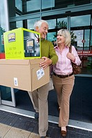 Mature couple leaving shop with boxes, smiling at each other, low angle view