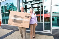 Mature couple leaving shop with television in box, smiling