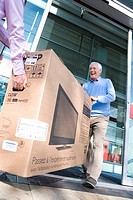 Mature couple leaving shop with television in box, low angle view