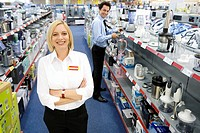 Young saleswoman in electronics aisle with arms crossed, smiling, porttrait