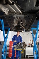 Mechanic with clipboard and part by elevated car, portrait, low angle view