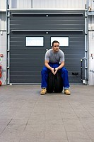 Mechanic in garage on tyres, portrait, low angle view