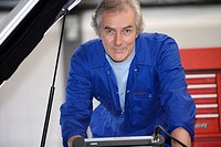 Mechanic with diagnostic computer by car with open bonnet, portrait
