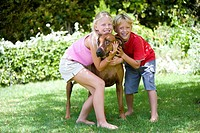 Girl 8-10 and brother 6-8 playing with dog outdoors, smiling