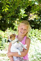 Girl 8-10 with dog outdoors, smiling, portrait