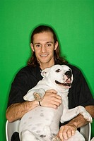 Caucasian mid_adult man holding white Pit Bull on lap.