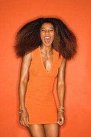 Sexy young African_American adult woman with big hair wearing dress on orange background laughing.