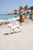 Woman running with poodle on beach, smiling