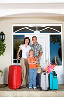 Family of three with luggage by front door of house, smiling, portrait