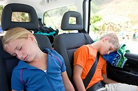Brother and sister 8-12 asleep in back of car, close-up