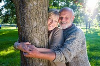 Mature couple embracing tree in field, smiling, portrait lens flare