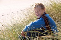 Boy 6-8 years sitting on long grass, smiling, portrait