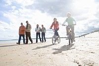 Boy and girl 7-9 years cycling by family walking on beach