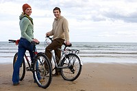Couple standing with bicycles on beach, smiling, portrait