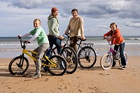 Family of four standing with bicycles on beach, smiling, portrait