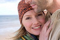Young couple embracing on beach, close-up of woman smiling, portrait