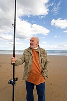 Senior man with fishing rod on beach