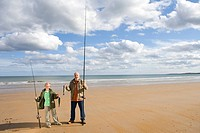 Grandfather and grandson 7-9 on beach with fishing rods and fish, smiling, portrait, elevated view