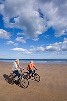 Senior couple cycling on beach, smiling at each other, elevated view