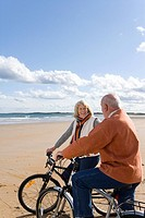Senior couple with bicycles on beach, smiling at each other