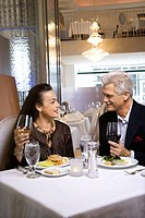 Caucasian mature adult male and Adult female sitting at restaurant table.