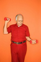 Mature adult Caucasian male lifting hand weights.