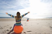 Girl and boy 8-12 on inflatable hoppers on beach, arms outstretched, rear view