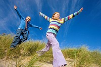 Boy and girl 8-12 running on sand dune, arms outstretched, low angle view