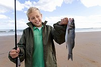 Boy 7-9 on beach with fishing rod and fish, smiling