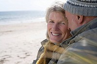 Senior couple on beach, portrait of woman smiling, close-up