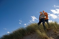 Senior couple on sand dune, man with hand on woman's shoulder, low angle view