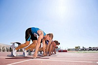 Male sprinters on starting blocks, low angle view sun flare