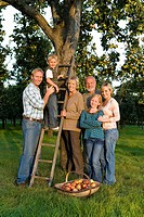 Family of three generations by ladder and apple tree, smiling, portrait