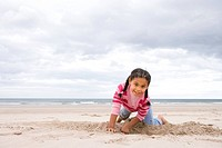 Girl 5-7 digging hole on beach, smiling, portrait