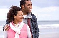 Young couple on beach, man with hand on woman's shoulder, smiling (thumbnail)