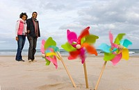 Pinwheels on beach, couple in background blurred motion