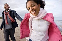 Young couple hand in hand on beach, portrait of woman smiling (thumbnail)