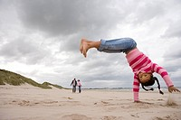 Girl 7-9 doing handstand on beach, portrait