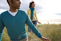 Young couple on sand dunes, smiling