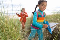 Sisters 5-9 with toy boats on sand dune blurred motion