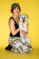 Hispanic mid_adult woman kneeling holding small white dog.