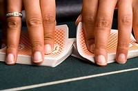 Female croupier shuffling cards on gambling table, close-up of hands
