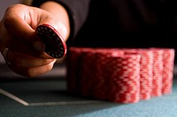 Woman placing gambling chip on table, close-up