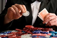 Man placing gambling chip on pile of chips on table, mid section (thumbnail)