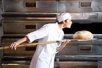 Female baker taking bread from oven, side view