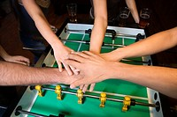 Group of young friends clasping hands in solidarity over foosball table.